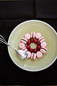 Pink macaroons and raspberries arranged in a circle on a plate