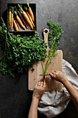 Fresh carrots on a dark background with chopping board and womans hands preparing