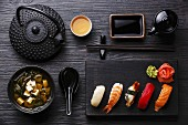 Nigiri Sushi set on wooden serving board and Miso soup on black wooden background