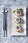 Mini rice sushi burgers with smoked salmon, green salad and sauces, black sesame served on white square plate