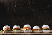 Mini rice sushi burgers with smoked salmon, green salad and sauces, black sesame served with wooden chopsticks