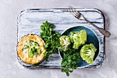 Baked homemade vegetable broccoli quiche pie in mini metal forms served with fresh greens