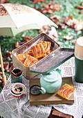 Apfel-Custard-Kuchenstücke mit Zimt in Metalldose auf Tisch im Freien