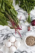 Ingredients for green shakshuka: beetroot leaves, eggs, herbs, onions, garlic and seeds