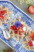Strawberry and elderflower waffles on a serving platter garnished with cornflowers and elderflowers