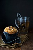 A salted caramel cupcake with a cup of herbal tea