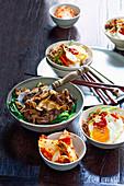 Koreanische Gerichte, Bibimbap (Hackfleisch, Reis und Ei) und Bulgogi (mariniertes Rindfleisch mit Pak Choi)