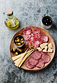 A cold cuts patter with salami, cheese and olives