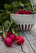 A bunch of radishes in a white speckled basket on an outdoor table with tall grasses behind