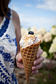 A woman holding a blueberry and vanilla ice cream cone, topped with graham cracker crumbs and a blueberry