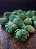 A pile of brussels sprouts on a wooden table