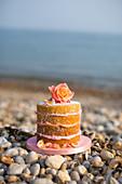 Schichtkuchen mit Rosenblüte am Strand