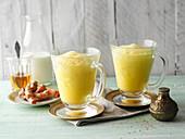 Golden milk with turmeric powder in glasses over dark grunge background