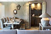Gedeckter Tisch im rustikalen Esszimmer mit Doppeltür zur Küche