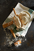 Flour in an old ceramic drawer with a wooden scoop and a rolling pin