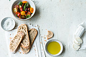 Slices of white bread with olive oil, tomato salad and goat's cheese