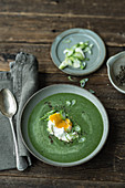Green vegetable soup with poached eggs