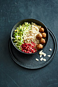 A healthy bowl with Brussels sprouts, freekeh balls and pomegranate seeds