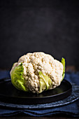 A cauliflower in front of a dark background