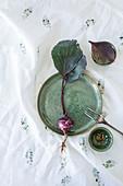 Schale und Teller mit violettem Kohlrabi auf bedrucktem Tuch