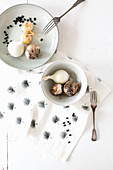 Schale und Teller mit Zwiebeln und Knoblauch auf bedrucktem Tuch