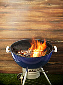 Flames on a charcoal barbecue in front of a wooden wall