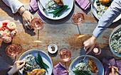 Tischszene mit Hähnchen, Reis, Oliven, grünen Bohnen und Wein