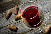 A red wine glass and corks on a rustic wooden table
