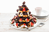 Profiterole pyramid cake with strawberries