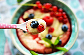 Custard with fresh fruits and fruit syrup on a spoon over a bowl
