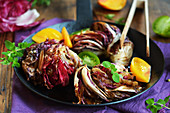 Fried radicchio with fresh tomatoes and herbs in a pan