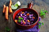 Red cabbage with carrots and apple in a ceramic pot with fresh ingredients in the background