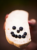 A blueberry smiley on a slice of buttered bread