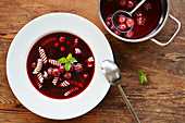 Cherry soup with noodles in a bowl and a saucepan