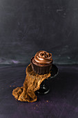 A chocolate cupcake with chocolate cream icing
