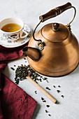 Grüner Tee in Kupferkessel und Teetasse