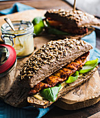 Marinated chicken breast in a wholegrain burger bun with mustard sauce and basil