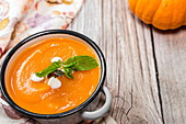 Homemade creamy pumpkin soup with mint in an enamel pot