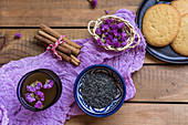 Green tea with cinnamon sticks, edible flowers and biscuits