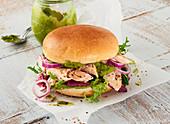 Brioche-Lachsburger mit Avocadocreme auf Papier
