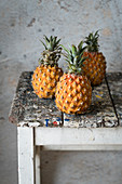 Three pineapples on an old stool