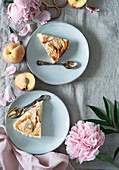 Two slices of peach tart with flaked almonds