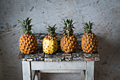 Four pineapples on an old stool