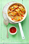 Sausages baked with cheese, corn, mushrooms and pepper