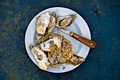 Gratinated oysters on a plate with a knife