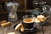 Espresso in a glass and cantuccini with a stove-top coffee maker in the background