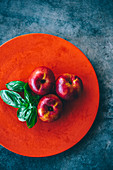 Nectarine and basil leaves on a red plate