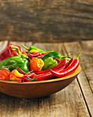 Sweet and chili peppers in a wooden bowl