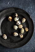 Quail eggs on a black plate