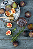 Fresh figs, honey and rosemary on wooden board